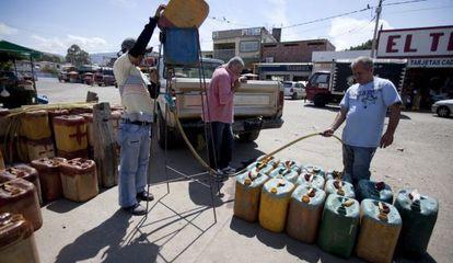 Contrabandistas rellenan tanques con gasolina en el lado colombiano de la frontera con Venezuela, en 2009.