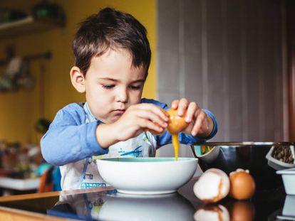 Un niño fríe un huevo.