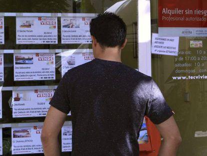 Un hombre mira el escaparate de una inmobiliaria en Madrid.