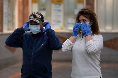 Dos personas se colocan la mascarilla en Sevilla.
