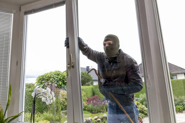 Un ladrón intenta entrar por la ventana de una casa, forzándola.