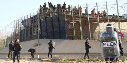 Un grupo de inmigrantes subidos al techo del puesto fronterizo, el jueves.
