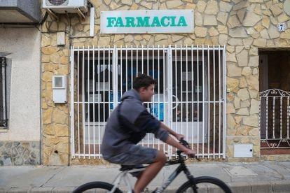 Un chaval en bicicleta pasa por delante de la farmacia de Balsa de Ves, cerrada permanentemente.