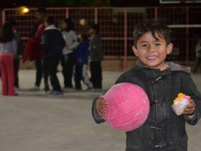 Un niño sostiene un balón en una noche de la Brigada de la Alegría en Nueva Galeana, un barrio de Juárez.