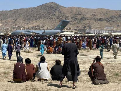 Cientos de afganos rodeaban este lunes un avión militar de transporte de EE UU en el aeropuerto de Kabul.