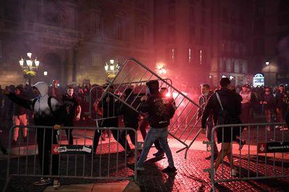 Diversas personas mueven vallas en la protesta en contra de las medidas por la covid.