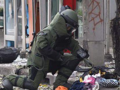 Un artificiero inspecciona el lugar de la explosión en Bangkok.