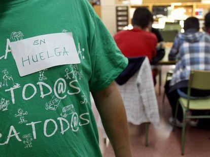 Isidro Álvarez, el dueño del taller de Vallecas (Madrid) donde se inventaron las camisetas de la marea verde, posa con una.