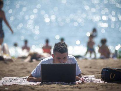 Un hombre mira un ordenador portátil en la playa