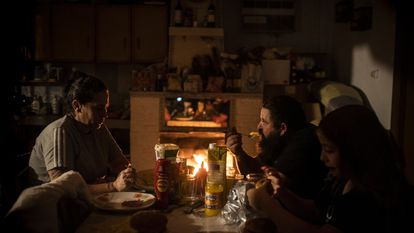 Rocío y su marido Jesús, junto a Jonny, el hijo menor, cenan en su domicilio de la Cañada Real a la luz la lumbre.