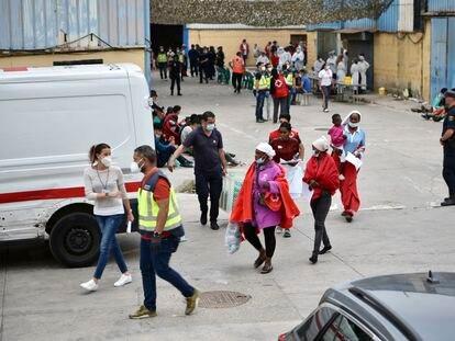 Profesionales sanitarios atienden a varias personas en la nave de primera acogida del polígono del Tarajal (Ceuta).