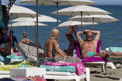Turistas ingleses toman el sol en una playa de Torremolinos (Málaga)
