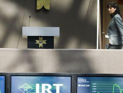 Una mujer pasa por delante de los paneles informativos de la Bolsa de México.