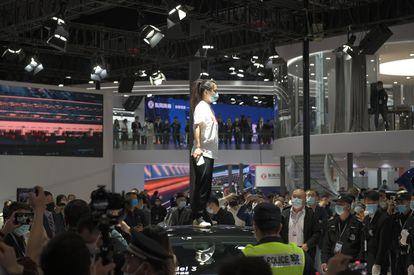 Una mujer protesta contra Tesla subida en un vehículo de la marca en el Salón del Automóvil de Shanghai.