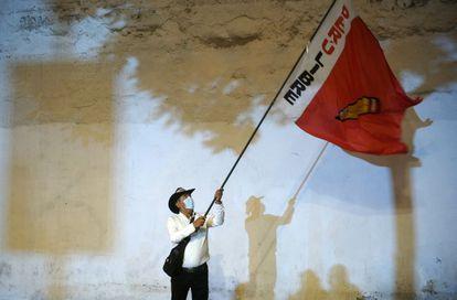 Un seguidor de Castillo ondea una bandera de su partido, el jueves en Lima.
