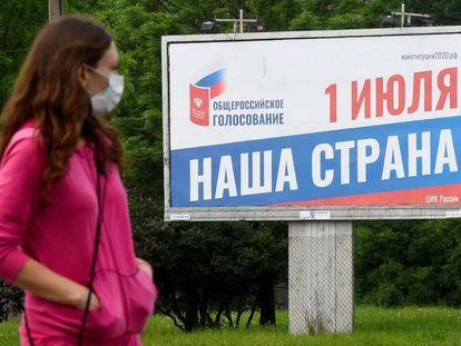 Una mujer pasa por un cartel sobre la reforma constitucional en San Petersburgo, el 10 de junio.