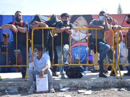 Migrantes esperan afuera de las oficinas del Instituto Nacional de Migración en Tapachula.