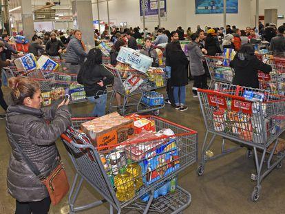 Clientes de un supermercado reúnen comida y agua en un Costco de Brooklyn, Nueva York, por temor a la expansión de coronavirus.
