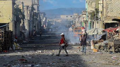 Residentes de un suburbio de Haití caminan por sus calles poco después de un tiroteo entre bandas criminales el 20 de diciembre de 2019.