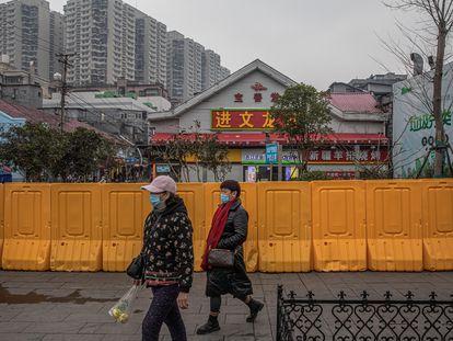 Unas mujeres con mascarilla pasan por delante de un área vallada en Wuhan.
