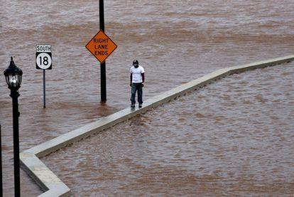 Un hombre camina por encima de una pared para poder desplazarse en New Brunswick, Nueva Jersey, durante las inundaciones provocadas por el paso del huracán Irene