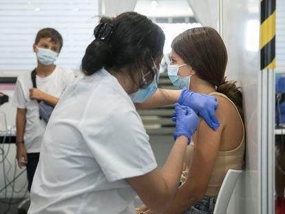 Una enfermera pone una vacuna contra la Covid-19 Coronavirus en la Fira. En la imagen una adolescente se vacuna con Pfizer.  / Massimiliano Minocri