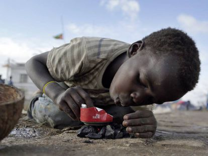 Un niño del distrito de Buzi, a 200 kilómetros de Beira (Mozambique), la zona arrasada por el paso del ciclón Idai hace una semana, intenta encender un fuego con restos de carbón para calentar algo de comida en una lata.