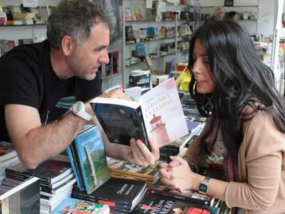 El escritor Mikel Alvira enseña la dedicatoria de su ultimo libro 'Llegará la lluvia' a una clienta.