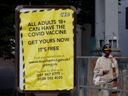 Un hombre pasa al lado de un cartel que anima a la población a vacunarse contra la covid, este lunes en Mánchester.