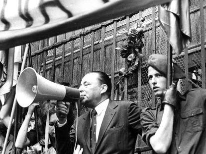 Carlos García Juliá sostiene una bandera en un mitin ultraderechista junto Blas Piñar, líder de Fuerza Nueva.