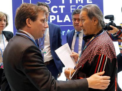 Un representante de los pueblos indígenas entrega un escrito en defensa de la Amazonia al alcalde de Madrid, José Luis Martínez-Almeida.