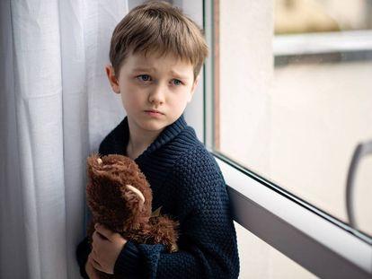 Niño está abrazando a su osito de peluche. De pie junto a la ventana.