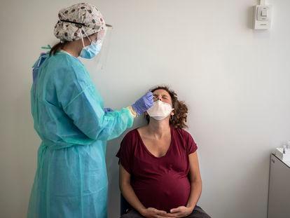 Personal medico del hospital Clinico San Carlos realizando una prueba pcr para detectar el Covid-19 a una mujer embarazada