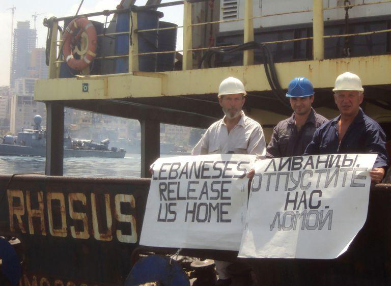 El capitán del 'Rhosus', Boris Prokoshev, y miembros de su tripulación muestran pancartas pidiendo su liberación en la embarcación que portaba 2.750 toneladas de nitrato de amonio, en el puerto de Beirut, en 2014.
