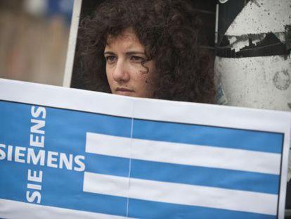 Una activista griega protesta en Berlín con una bandera que incluye el nombre de una empresa alemana.