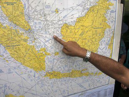 Un oficial señala un mapa del probable lugar del accidente.