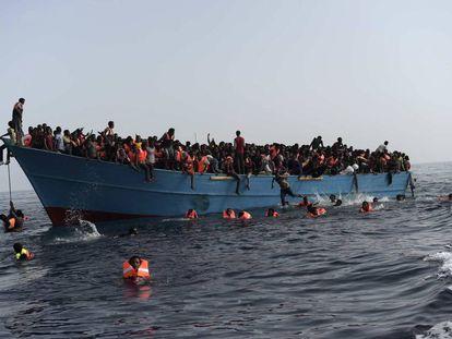 Migrantes en alta mar esperan a ser rescatados en una operación coordinada por la Marina italiana.