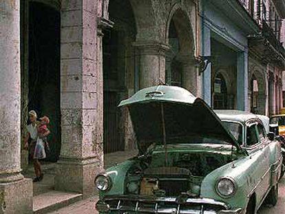 Dos cubanos reparan su coche en una calle de La Habana Vieja.