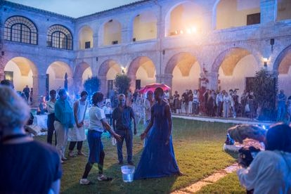 La bailarina Amie Mbye interactúa con un espectador en su actuación bajo la lluvia en el lazareto de Mahón durante los encuentros sobre Camus.