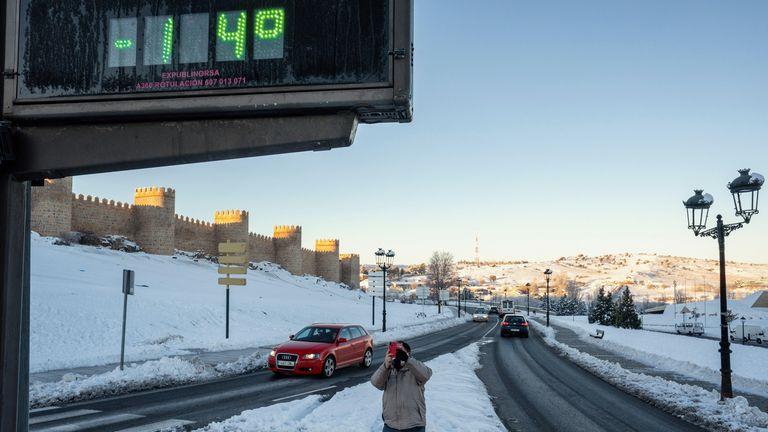 ÁVILA, 12/01/2021.- Un hombre toma un fotografía con su móvil de un termómetro que marca 14 grados bajo cero, este martes junto a la muralla de Ávila. EFE/ Raúl Sanchidrián