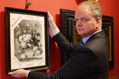 El director de los Uffizi, Eike Schmidt, sostiene una reproducción de 'Jarrón con flores', con el rótulo de