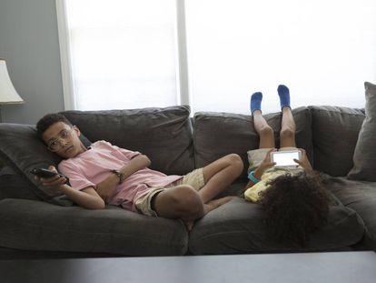 Dos adolescentes están aburridos en el silón.
