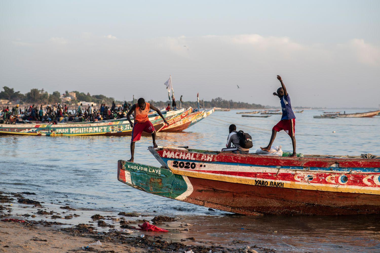 Muchachos merodeando por las embarcaciones que los migrantes utilizan para salir hacia Canarias desde Mbour, en Senegal. / SYLVAIN CHERKAOUI