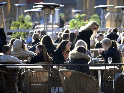 Clientes de un restaurante toman el sol en las terrazas abiertas en el centro de Estocolmo, el 26 de marzo de 2020.