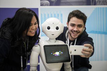 El robot Pepper, con dos estudiantes.
