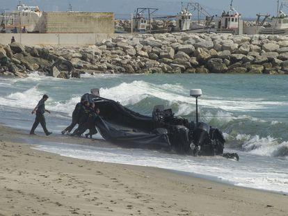 Agentes de la Guardia Civil arrastran una lancha abandonada por los narcos tras una persecución, en la playa del Tonelero, en La Atunara (Cádiz).