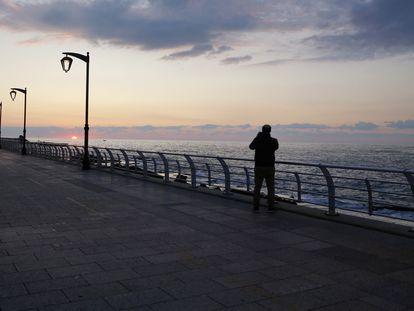 Un hombre pasea solo por el paseo marítimo de Beirut (Líbano), que ha tomado estrictas medias de confinamiento para evitar que se extienda el coronavirus.