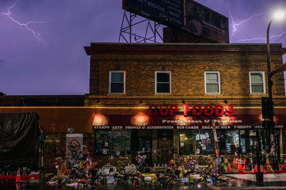 La fachada de Cup Foods, la tienda donde tuvo lugar el incidente con un billete falso que provocó el arresto mortal de George Floyd, rodeada de flores y mensajes la noche del pasado 5 de abril.