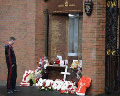 Un seguidor del Liverpool, ante el memorial en homenaje a las víctimas de Hillsborough situado en uno de los accesos a Anfield