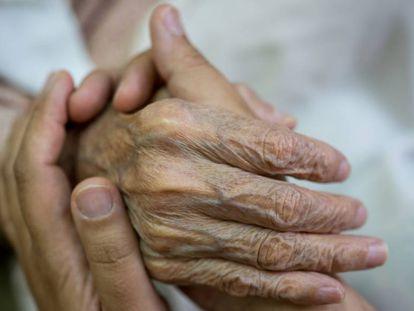 Una persona da la mano a un anciano.